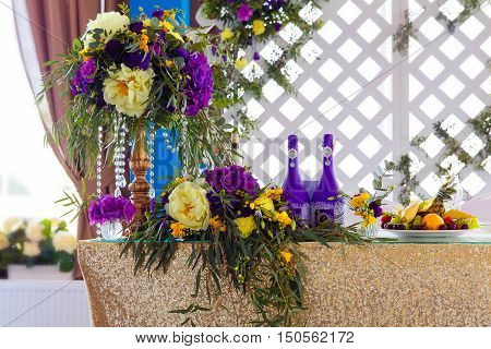 Floral arrangement to decorate the wedding feast the bride and groom. Flowers candles a bottle of champagne. The vintage.