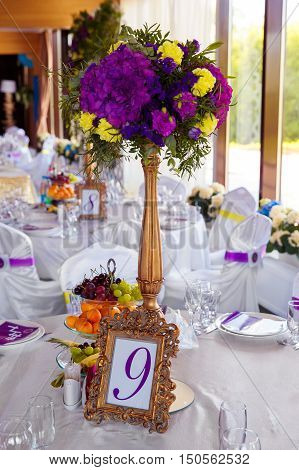 Floral arrangement and gold frame with a number of the decorated wedding table for guests. Vintage poster