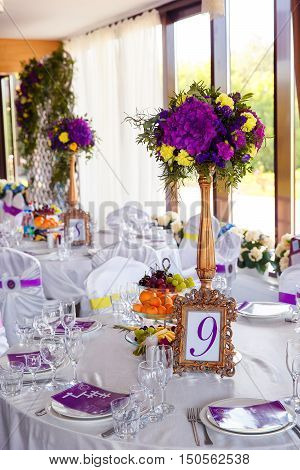 Floral arrangement and gold frame with a number of the decorated wedding table for guests. Vintage