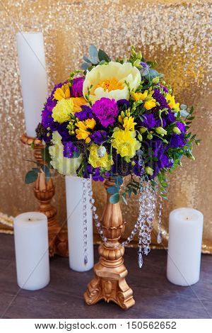 Floral arrangement to decorate the wedding feast the bride and groom. Flowers and candles. The vintage.
