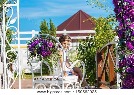 Girl sitting on chair under arch for wedding ceremony decorated with flowers in the background. Floristic composition in vintage style. The Provence.