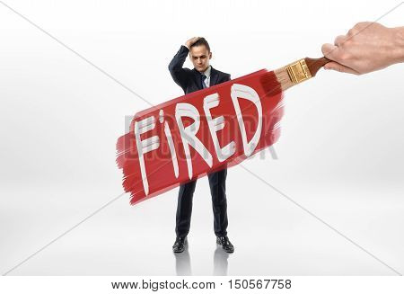 Hand drawing red line with sign 'fired' over the businessman. Losing a job. Jobless. Discharging. Unemployment.