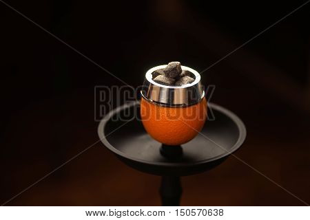 Preparation for Smoking fruit orange aroma hookah. Set fruit with coals.