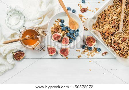 Healthy breakfast set. Oat granola with nuts, yogurt, honey, fresh figs and blueberries in bowl on white wooden background, top view, copy space, horizontal composition
