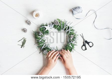 Christmas. Child making handmade christmas wreath. Top view flat lay