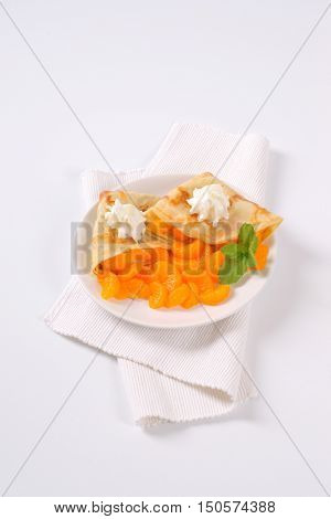plate of pancakes with canned tangerines on white place mat