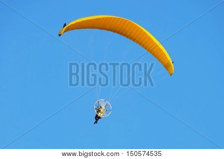 Flight on a motorized paraglider. Yellow paraglider with a paramotor.