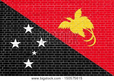 Papua New Guinean national official flag. Papuan patriotic symbol banner element background. Accurate dimensions. Correct size colors. Flag of Papua New Guinea on brick wall texture background, 3d illustration