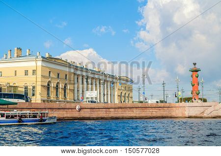 ST PETERSBURG RUSSIA - OCTOBER 3 2016. St Petersburg landmarks of Vasilievsky island spit - rostral column and building of Zoological Museum former South Exchange Warehouse in St Petersburg Russia