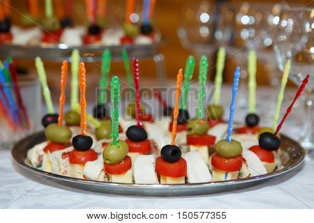 Canapes - sandwiches on skewers on a platter. Culinary food buffets. Sandwiches of toast, cut and different food base (fish, meat, cheese) impaled on Atle.
