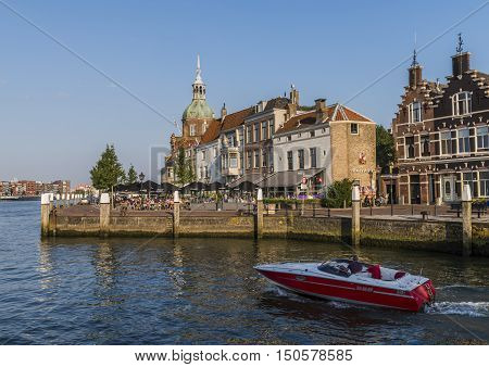 Dordrecht The Netherlands - September 13 2016: Terrace in Dordrecht with Groothoofdspoort and motor boat on the water of the Merwede in Zuid-Holland The Netherlands.