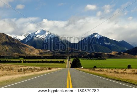 A Long Road Leads to Green Pastures and The Southern Alps.  Arthurs Pass, Canterbury, New Zealand
