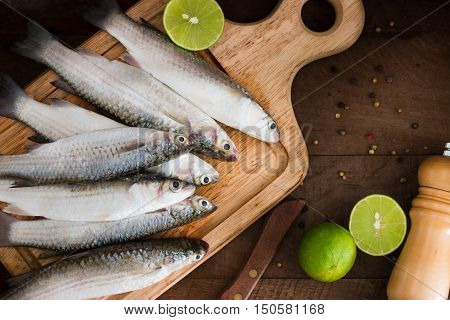 Seafood fresh mullet fish with lime and spice on a old wooden table. top view