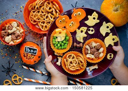 Child hands puts on the table plate with variety of treats at Halloween theme party top view
