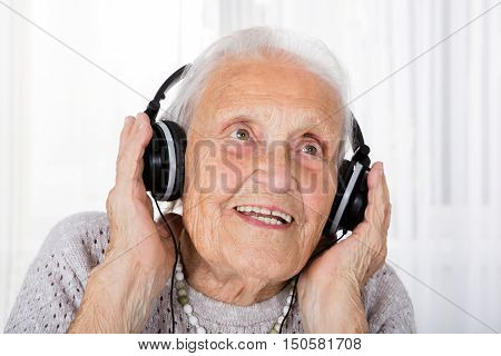 Portrait Of Happy Senior Woman Listening Music With Headphone At Home