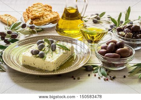 Feta cheese in the plate, two kinds of olives, olive oil, crackers framed by branches of olive tree on a light white wooden background. Feta cheese, olives and olive branches. Horizontal. Daylight.