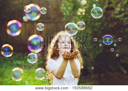Child stretched his hand and catches soap bubbles in the summer on nature. Happy childhood peace world help concept.