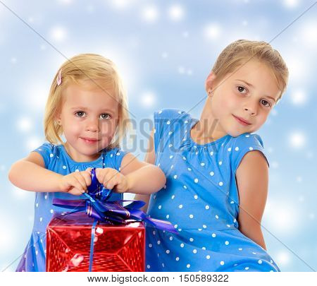 Two charming little girls , sisters, in identical blue dresses with polka dots. Girl looking at gifts Packed in beautiful red paper tied with a bow.On a blue background with large, white, Christmas