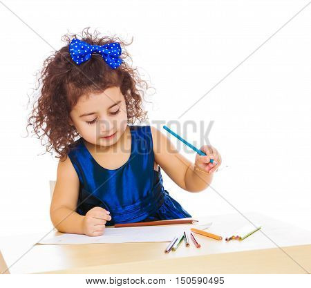 Pensive little girl in a blue dress, holding a pencil . She paints at a table in a Montessori kindergarten.Isolated on white background.