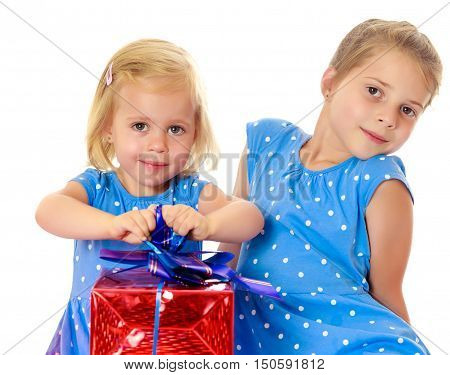 Two charming little girls , sisters, in identical blue dresses with polka dots. Girl looking at gifts Packed in beautiful red paper tied with a bow.Isolated on white background.