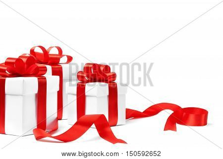 White gift boxes with red ribbon bows isolated on white background with copy space