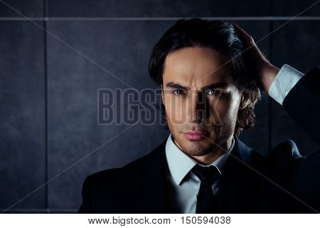 Handsome brutal man in black suit combing hair with fingers poster
