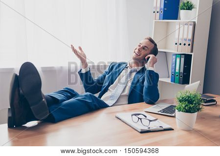 Happy Businessman Talking On Phone And Holding Legs On Table