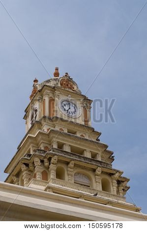 Madurai India - October 21 2013: The clock tower of the Nayak Palace against blue sky. Dials show seven o'clock.