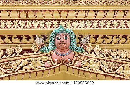 Madurai India - October 21 2013: At the Nayak Palace a human torso with long green hair hidden between abundant decorations form the upper plinth.