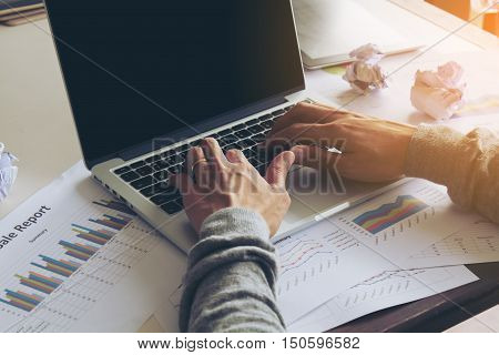 Businessman typing on keyboard laptop working on business report. The blank screen with copy space for your text or advertising content. Selective focus and soft flare filter.