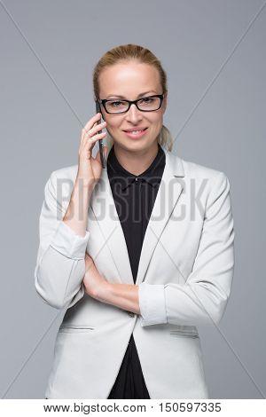 Beautiful young caucasian businesswoman in business attire wearin black eyeglasses, talking on mobile phone. Studio portrait shot on grey background.