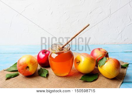Glass honey jar with dipper and apples copy space. Rosh hashanah concept. Jewish new year symbols.