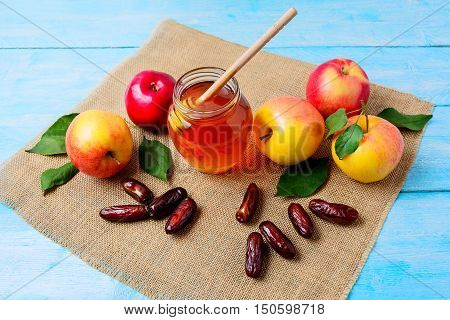 Glass honey jar dates and apples on burlap napkin. Jewish new year symbols. Rosh hashanah concept. Organic fruits.