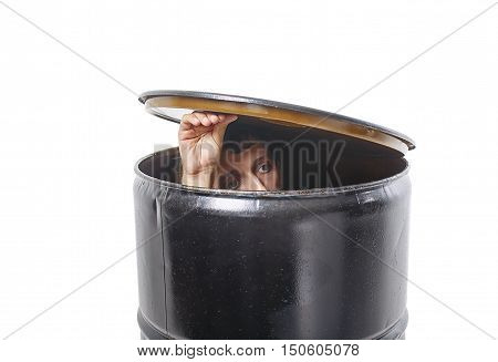 young man hides in a barrel. guy lifted the lid barrels and looks cautiously. the concept of avoiding problems. isolated on white background.