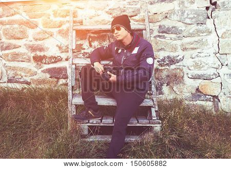 fashion people photography technology leisure and lifestyle - young hipster man holding digital camera sitting on stairs old wall be-hide blur and vintage style