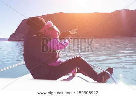 Father with daughter on the bow of the ship. hold daughter with hand and point finger on sunset background. lover and family concept mean love from father