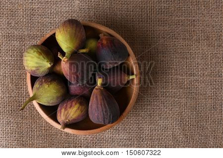 A wood bowl full of fresh picked figs. horizontal format with copy space.