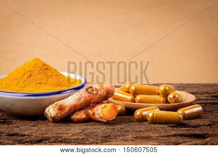 the turmeric powder and capsule and roots curcumin on wooden plate