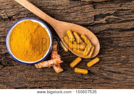 the turmeric powder capsule and roots curcumin on wooden plate