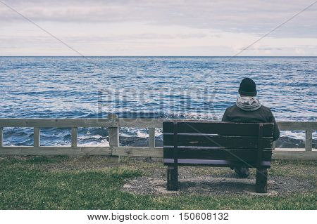Man sitting on bench overlooking sea with toned effect