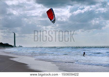 Kite boarding along Ashkelon coastline sea in Israel.