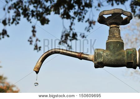 Concept photo of waste of water - Leaky water tap in the garden.