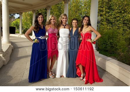 Beautiful Teenage Girls at the Prom.  They are posing for a photo outside.