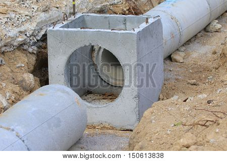concrete drainage pipe sections lying in a ditch during new road construction, near Songkhla, Thailand