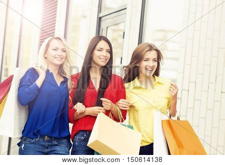Attractive girls walking in a city center. Women with a shopping bags. Friends spending money. Discount, sale and shopping concept.