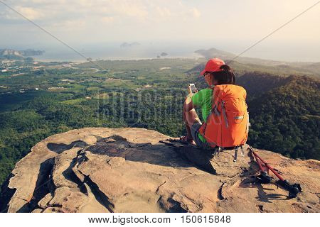 hiker taking photo with smartphone at seaside mountain cliff