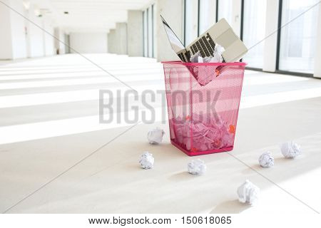 Laptop and crumpled papers in wastepaper basket at office