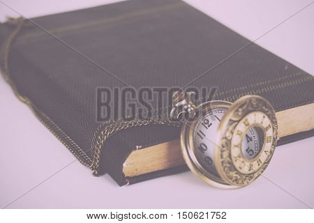 Pocket watch and book against a light coloured background Vintage Retro Filter.