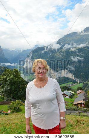 Senior woman standing admiring a mountaintop view. Travel concept