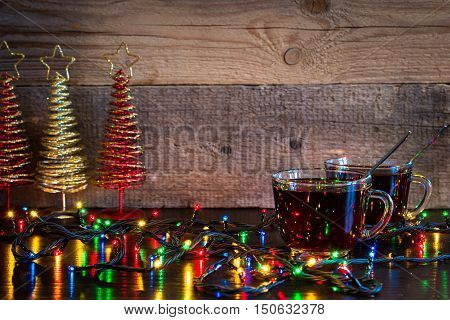 Christmas background with two cups of tea and lights on wood texture with place for text